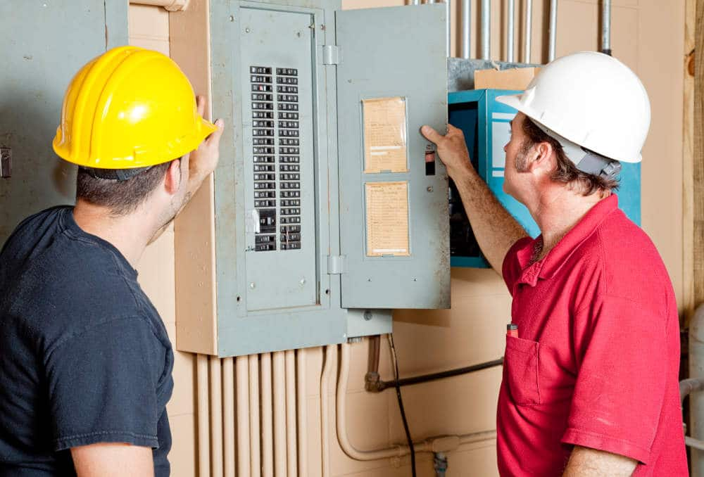Electricians examining a circuit breaker panel i