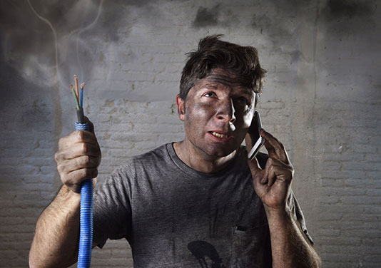 man holding exposed wires talks on phone