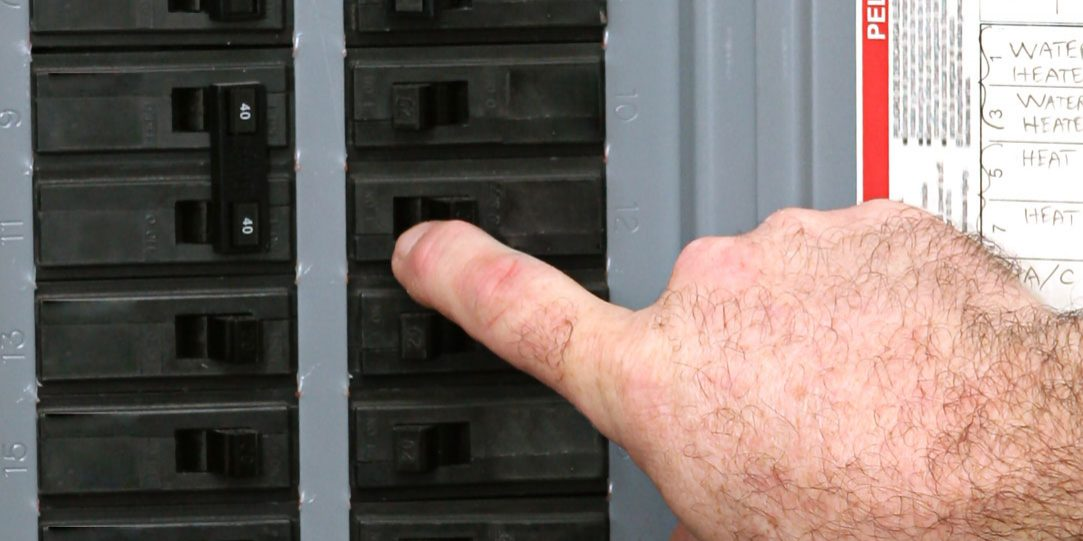 Electricians examining a circuit breaker panel in an industrial setting.