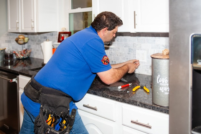 Hot Shot Electric working on kitchen receptacle